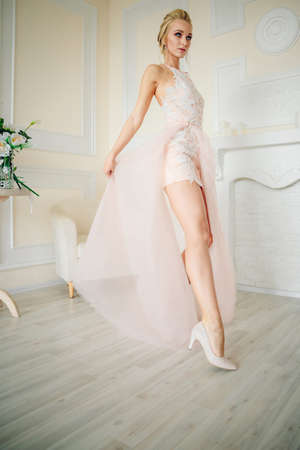 A slender and tall bride in a beige short dress holds the hem of the dress and looks seriously with her graceful leg forward