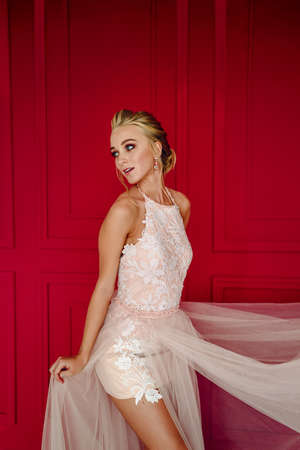 An attractive bride coquettishly holds the hem of her dress. Stunning blonde in a short dress against a red wall. The girl in the short dress was suddenly called out.