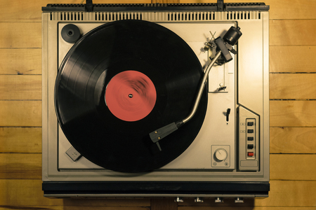 Vintage vinyl player on wooden background top view