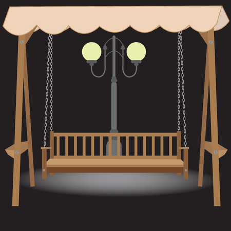 light chains: wooden bench swing with a roof made of cloth suspended on chains in the light of the night lamp