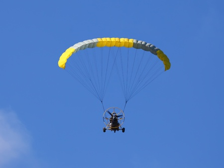 Flying paraplane on blue sky background