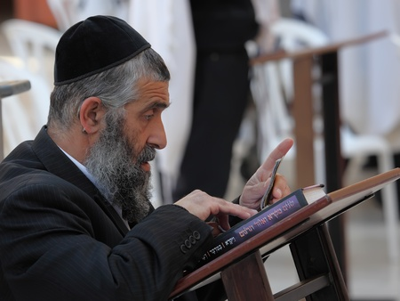Unidentified Jewish man reading the sacred writings on the Western Wall during a Jewish holiday on May 13, 2011 in Jerusalem, Israel