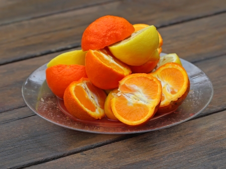 A fruit plate of oranges and lemons on a wet wooden table after rain photo