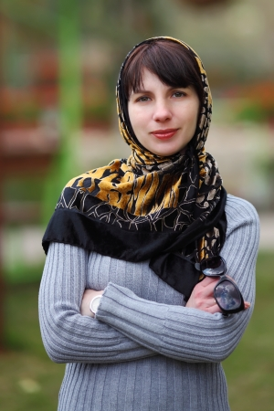 Portrait of young woman in park with a scarf on a head  photo