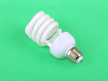 Energy saving fluorescent light bulb on green background photo