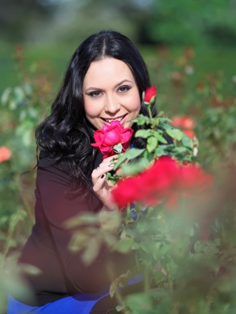 Beautiful young woman enjoying the scent of a red rose