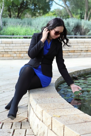 young woman near the fountain,put her hand into the water Stock Photo - 16753861