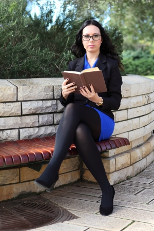 Portrait of young attractive brunette woman with glasses holding a old book Stock Photo - 16753862