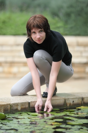 young woman near the fountain,put her hand into the water  Stock Photo - 17159475