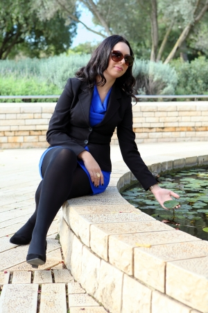 young woman near the fountain,put her hand into the water Stock Photo - 17289057