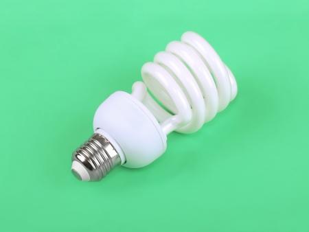 the lumen: Energy saving fluorescent light bulb on green background