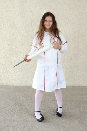 Little girl dressed up in nurses costume photo