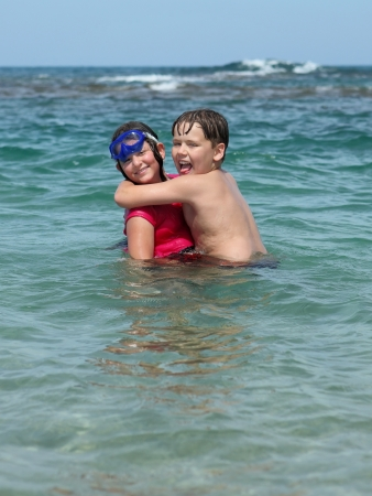 Happy young children, boy and girl playing and swimming in the transparent sea  photo