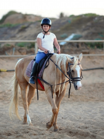 little girl is riding a horse  Stock Photo