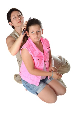 jewess:  woman brushing her daughters hair against a white background  Stock Photo