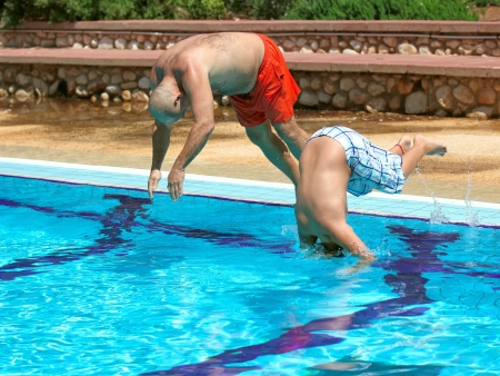 Father And Son jumping in the pool photo