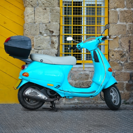 Retro Blue scooter parked at the front of the House