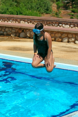 Young girl in mid-air above a swimming pool  photo