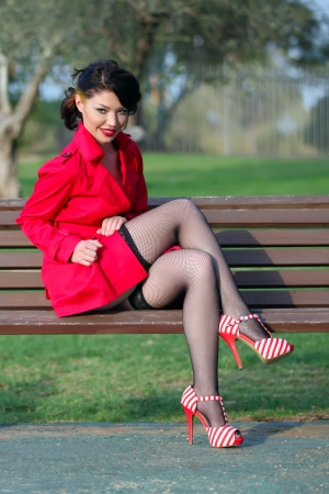 jewess: Beautiful young women in red coat posing in park
