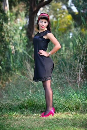 jewess: young beautiful pin-up brunette woman posing in black dress  Stock Photo
