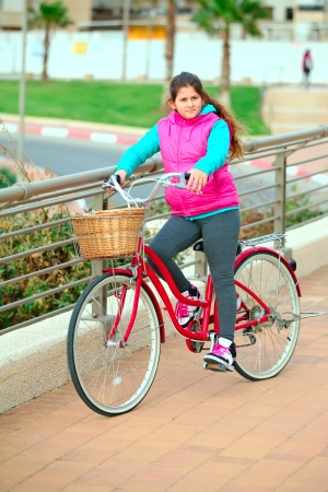 Cute little  girl on her red bike on the road  Stock Photo