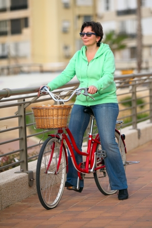 jewess: Woman with her bike and looking away  Stock Photo