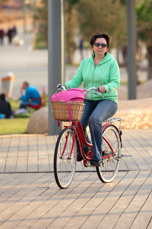 jewess: Urban biking - middle-aged women and bike in city