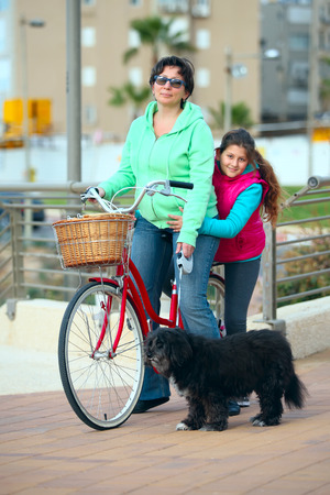 jewess: a mother, a daughter and a dog with a bike on the street Stock Photo