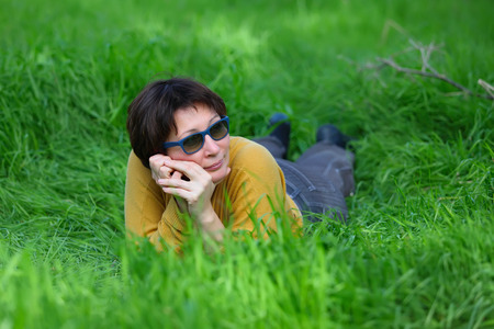 middle aged woman lying on a green grass