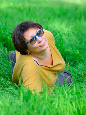 middle aged woman lying on a green grass photo
