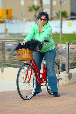 jewess: Woman with her bike and a dog on the street  Stock Photo