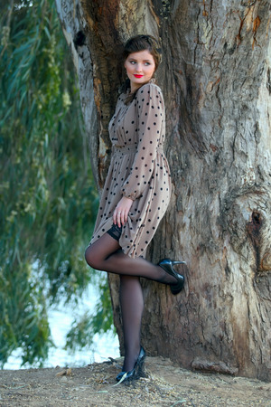 young woman posing near a tree