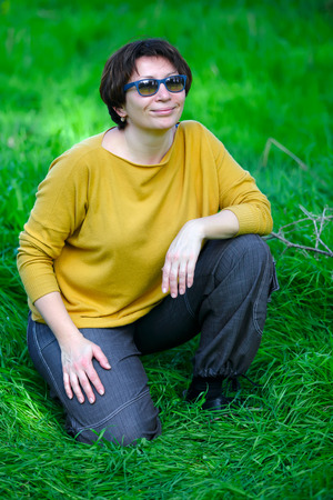 middle aged woman sitting on green grass photo