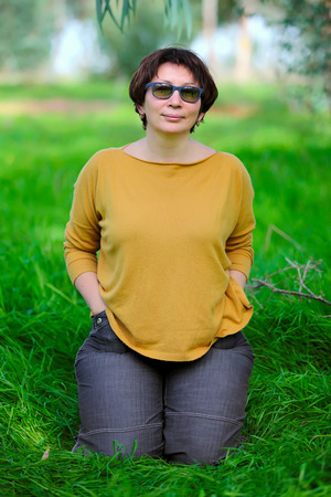 jewess: middle aged woman sitting on green grass Stock Photo