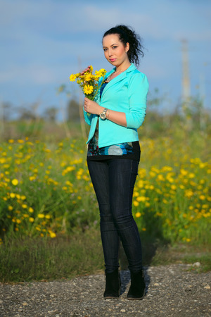 young brunette with a bouquet of wildflowers  photo