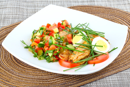 Salad with grilled chicken breast,mixed greens and hard boiled eggs  on white dish