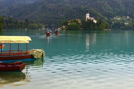 Catholic church situated on an island on Bled lake,Slovenia with tourist boats on lake photo