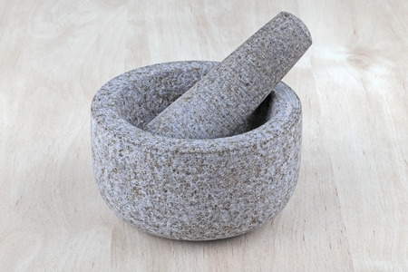 An empty stone mortar and pestle on wooden table photo