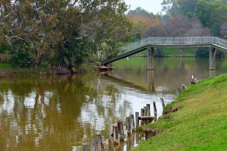 vlonder: Houten loopbrug over een vijver in het stadspark