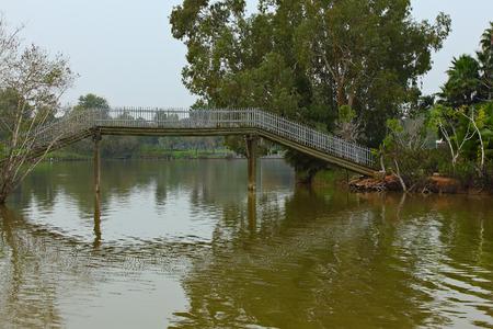 wooden Footbridge over a pond in city park