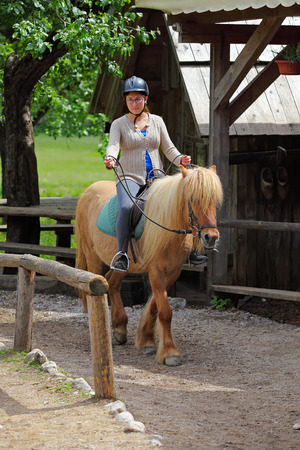 Young woman getting a horseback riding lesson