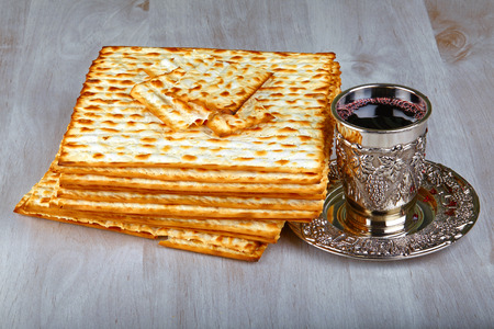 matzo: passover matzo with kiddush cup of wine on wooden table