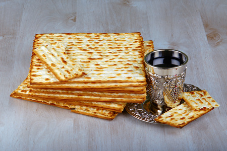 jewry: passover matzo with kiddush cup of wine on wooden table