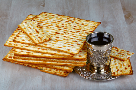 kiddush: passover matzo with kiddush cup of wine on wooden table