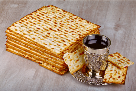 matzot: passover matzo with kiddush cup of wine on wooden table