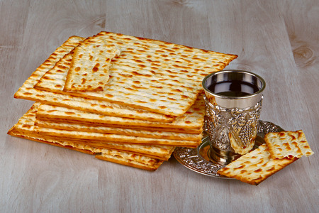 matzot: Closeup of Matzah with kiddush cup of wine on wooden table