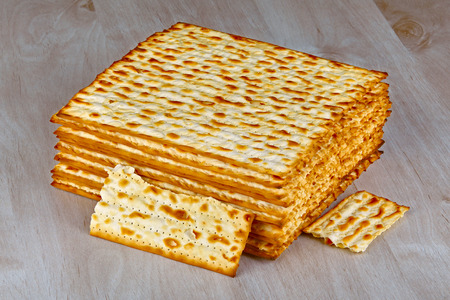 unleavened: Closeup of Matzah on wooden table which is the unleavened bread served at Jewish Passover dinners Stock Photo