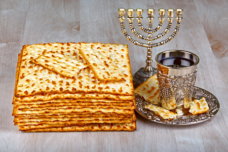pesakh: passover matzo with kiddush cup of wine on wooden table