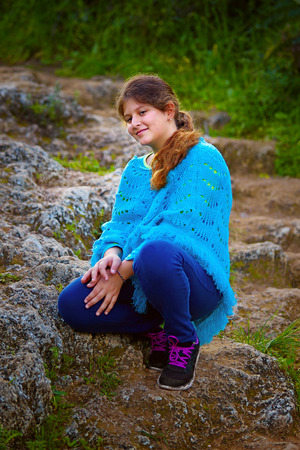 jewess: little girl sitting on stone road in a park. Stock Photo
