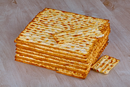 pesakh: Closeup of Matzah on wooden table which is the unleavened bread served at Jewish Passover dinners Stock Photo